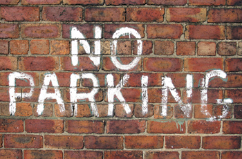 No parking brick wall white spray paint