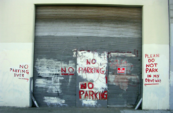 No parking on a big garage door spray painted all over the wall