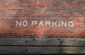 No parking painted on brick wall in white letters