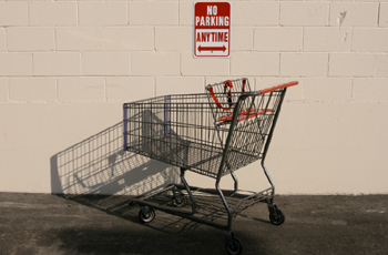 No parking sign on wall in front of shopping cart